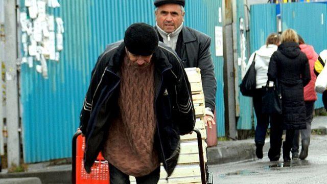 мужчина тащит тележку на рынке