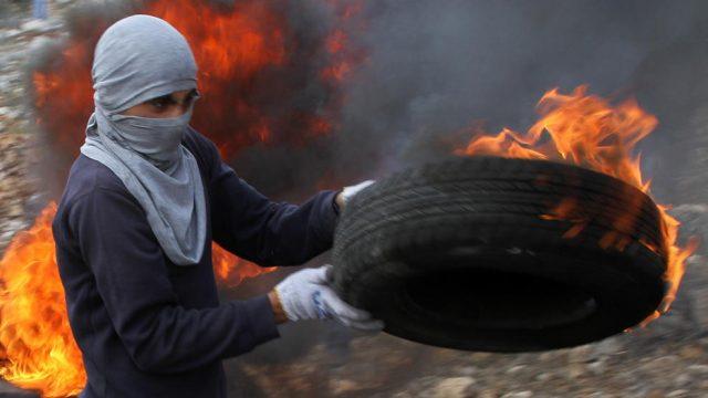 палестинец держит горящую шину