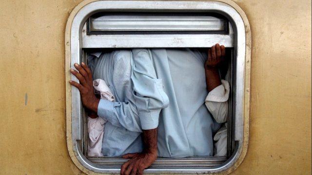 мужчины застряли  у окна вагона