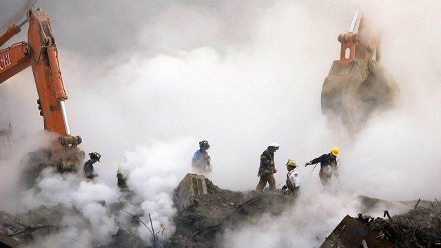 Спасатели пробираются сквозь руины торгового центра, охваченные облаком пыли и дыма. Нью Йорк, 11 сентября 2001 г.