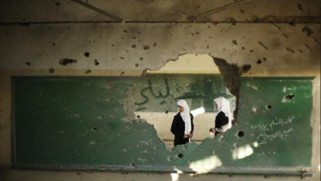 палестинские студенты смотрят на разрушенную стену класса