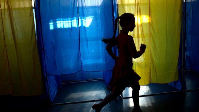 девочка пробегает мимо кабин для голосования